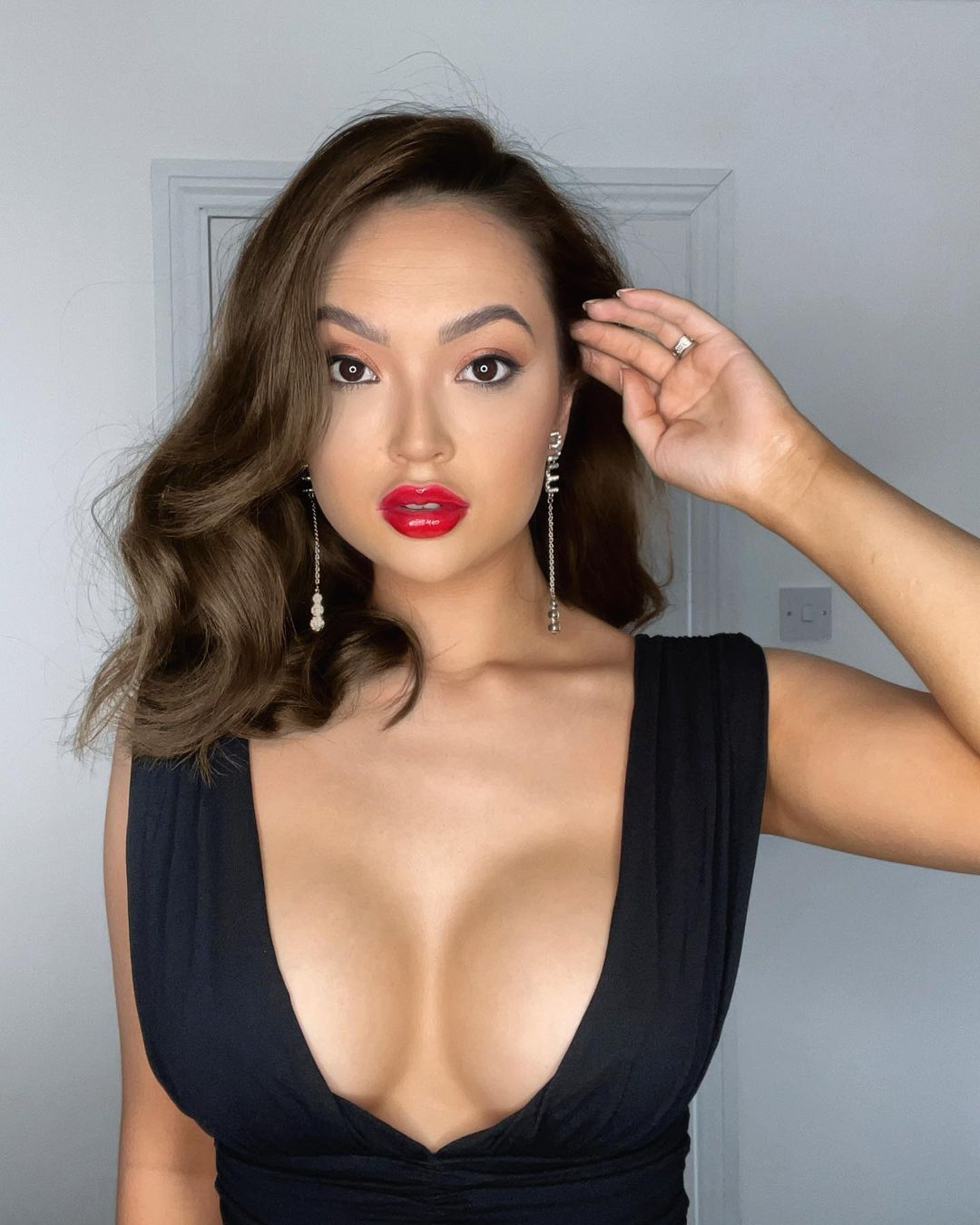 Love Island Contestant Sharon Gaffka in a low cut black dress and red lipstick