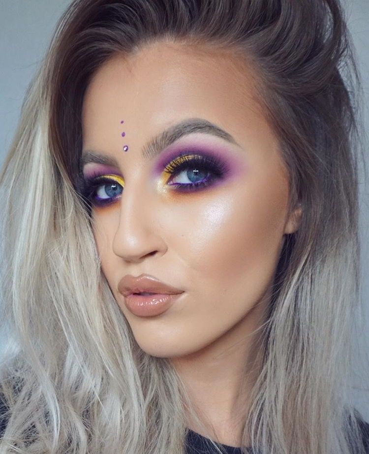 An image of girl showing her festival makeup using bright eyeshadow colours