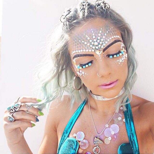 An image of a woman showing her festival makeup look including glitter and gems